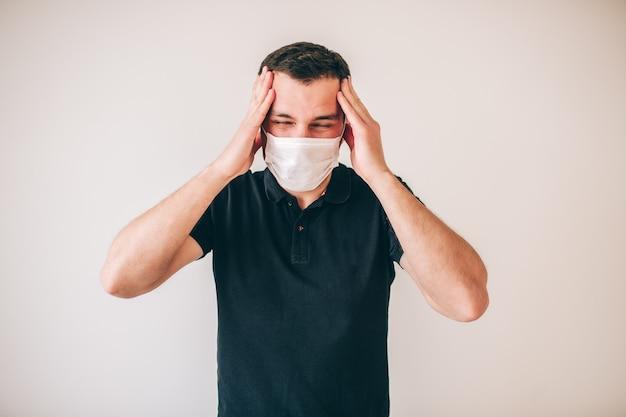 Giovane uomo malato isolato sopra la parete. ragazzo in camicia nera soffre di mal di testa. mani forti sulla testa.