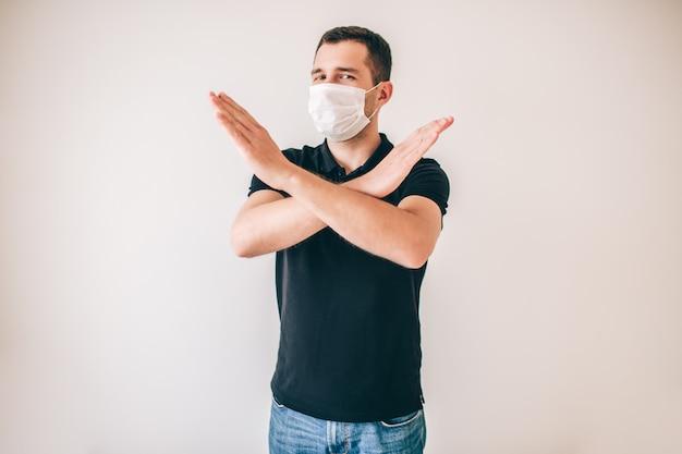 Giovane uomo malato isolato sopra la parete. ragazzo in camicia nera indossare maschera di protezione medica. tenere le mani incrociate mostrando stop o simbolo proibito.