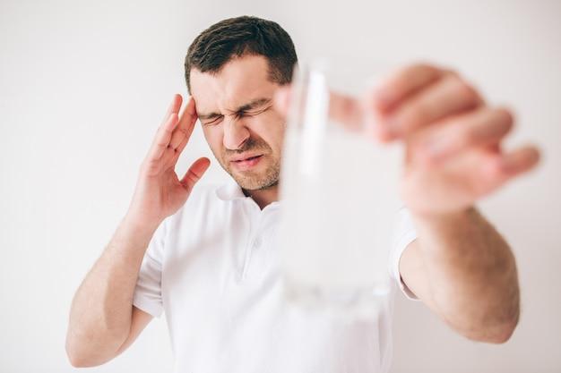 Giovane uomo malato isolato sopra la parete. guy tenere il vetro sfocato con acqua e pillole effervescenti in esso. tenere con mal di testa o dolore. tieni un'altra mano vicino alla testa.