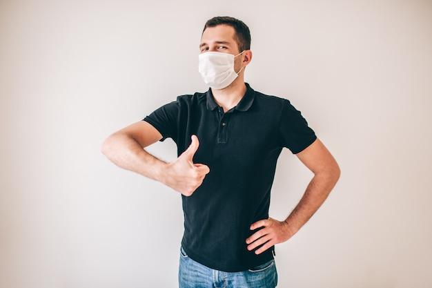 Giovane uomo malato isolato sopra la parete. il ragazzo positivo in camicia nera tiene il grande pollice in su. il giovane indossa una maschera medica di protezione bianca per evitare la malattia.