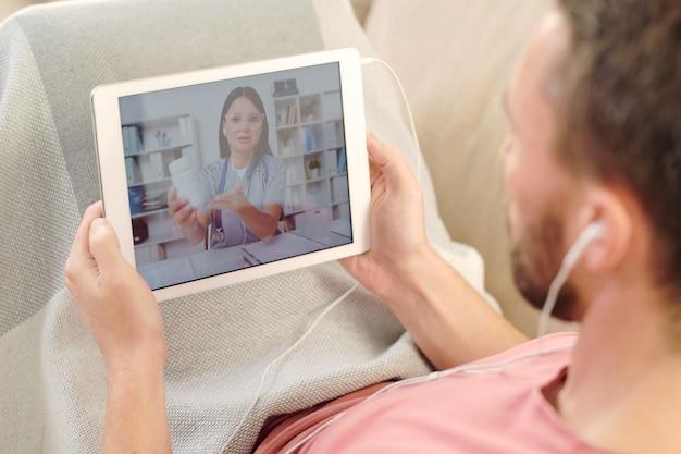 Giovane uomo malato con tablet digitale seduto sul divano sotto la coperta mentre si riposa e ascolta i consigli del medico online sulla medicina