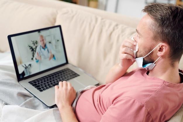 Giovane uomo malato con il computer portatile che si soffia il naso mentre è seduto sul divano sotto la coperta, riposando e ascoltando le raccomandazioni del medico online