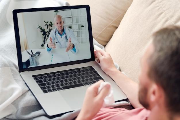 Giovane uomo malato con laptop e fazzoletto spiegazzato seduto sul divano sotto la coperta mentre si riposa e consulta un medico online