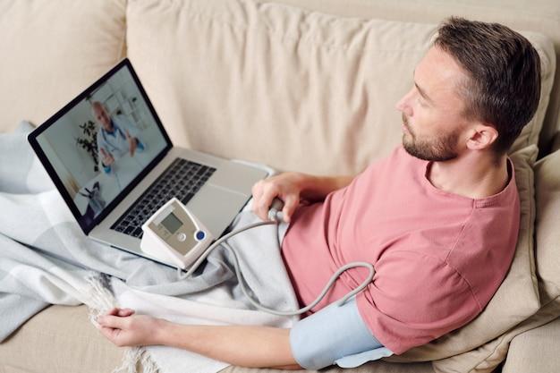 Giovane malato con tonometro che misura la sua pressione sanguigna mentre è seduto sul divano sotto la coperta e ascolta i consigli del medico online