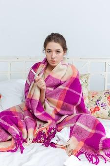 Giovane donna malata in coperta con termometro