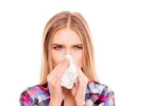 Giovane donna malata che ha allergia e starnuti nel tessuto
