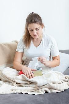 Giovane donna malata seduta sul divano coperta da una coperta e tirando i fazzoletti dalla scatola
