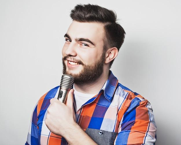 Giovane cantante uomo con microfono su sfondo grigio
