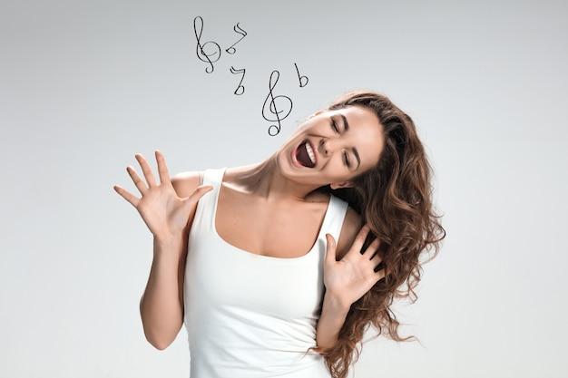 La giovane donna che canta con divertenti emozioni felici su sfondo grigio
