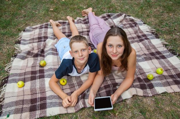Giovane sorella e fratello con le lentiggini sui loro volti sdraiati su plaid e utilizzando tablet nel parco. vista dall'alto, guardando la fotocamera con un sorriso.