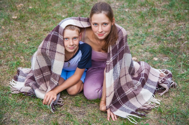 La giovane sorella e il fratello con le lentiggini sui loro volti stanno ricoperti di plaid nel parco, si scaldano, sorridono e guardano la telecamera.