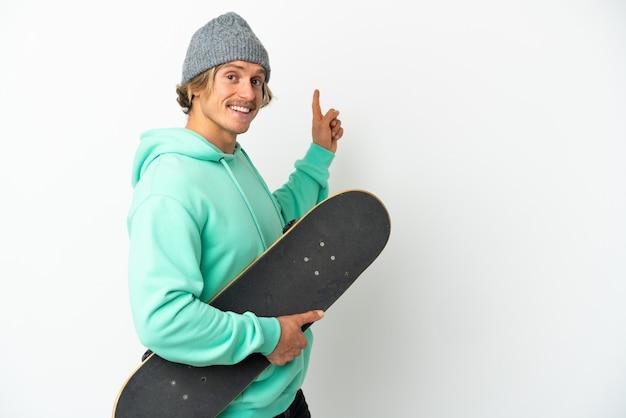 Uomo biondo del giovane pattinatore isolato sulla parete bianca che indica indietro