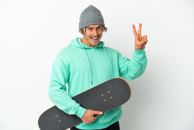 Uomo biondo giovane pattinatore isolato sul muro bianco sorridente e mostrando il segno di vittoria