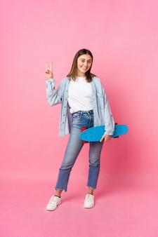 Donna giovane pattinatore isolata sulla parete rosa
