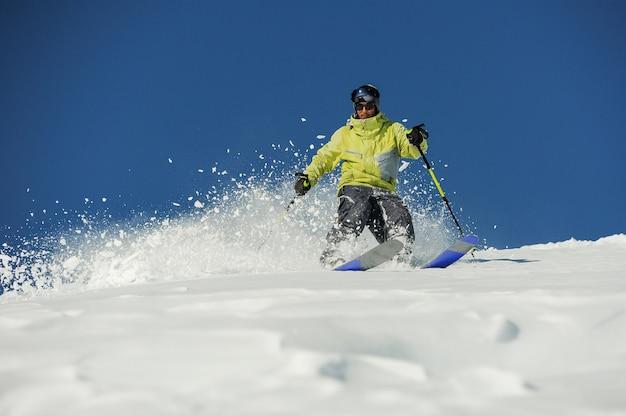 Giovane sciatore in abiti sportivi gialli a cavallo lungo il pendio in georgia, gudauri