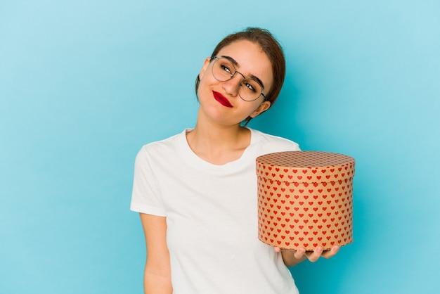Giovane ragazza araba magra che tiene una scatola di san valentino sognando di raggiungere obiettivi e scopi