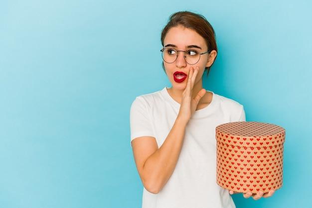 La giovane ragazza araba magra che tiene una scatola di san valentino sta dicendo una notizia segreta di frenata calda e sta guardando da parte