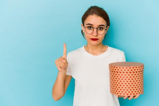 Giovane ragazza araba magra che tiene una scatola di san valentino che mostra il numero uno con il dito.