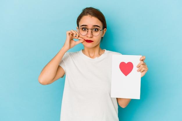Giovane ragazza araba magra che tiene una carta di san valentino con le dita sulle labbra mantenendo un segreto.