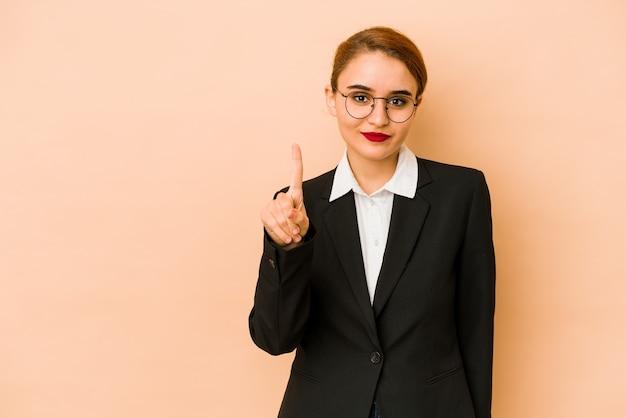 Giovane donna caucasica magra di affari isolata che mostra numero uno con il dito.