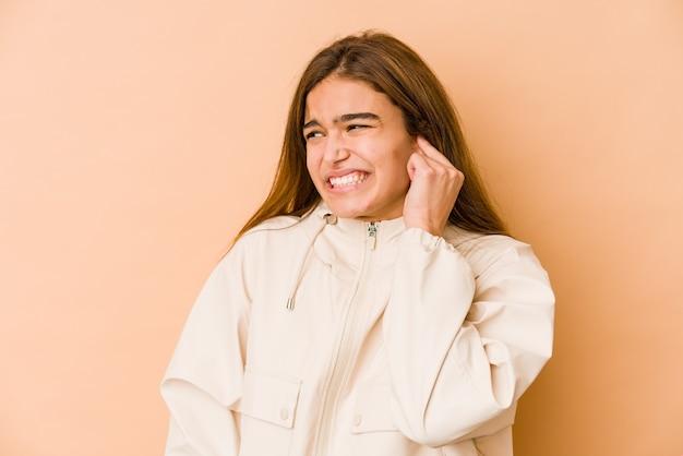 Giovane ragazza caucasica magra dell'adolescente che copre le orecchie con le mani.