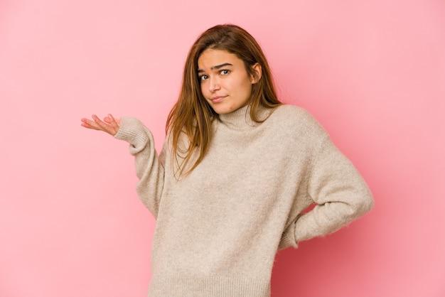 Giovane ragazza adolescente caucasica magra dubitando e scrollare le spalle nel gesto interrogativo.