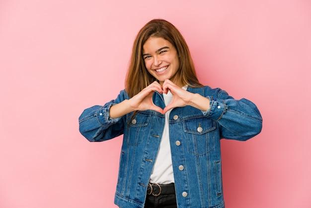 Ragazza giovane adolescente caucasica magra che sorride e che mostra una forma del cuore con le mani.