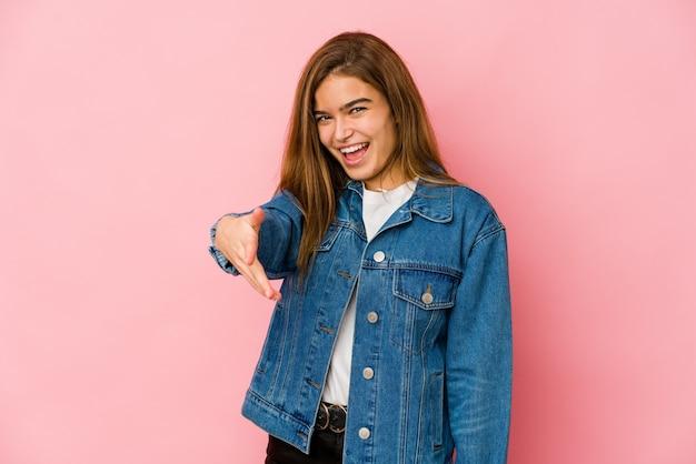Ragazza giovane adolescente caucasica magra che allunga la mano alla macchina fotografica nel gesto di saluto.