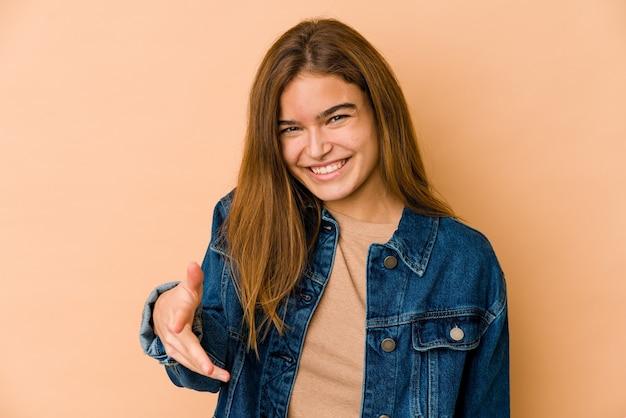 Giovane ragazza adolescente caucasica magra che allunga la mano nel gesto di saluto.