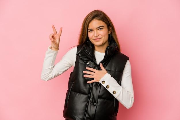Giovane ragazza adolescente caucasica magra prestando giuramento, mettendo la mano sul petto.