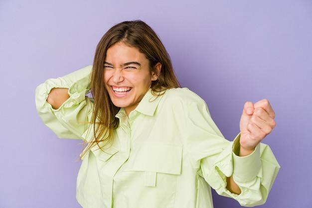 Adolescente giovane ragazza magra sulla parete viola ballando e divertendosi