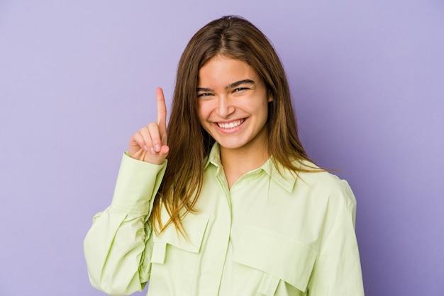 Giovane adolescente ragazza magra sulla parete viola che mostra il numero uno con il dito