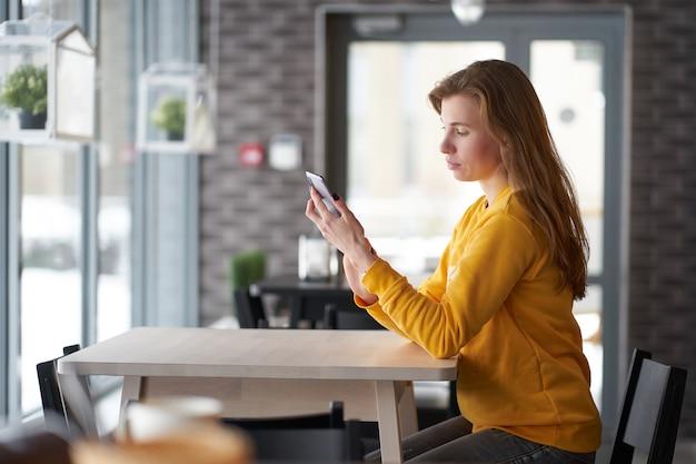 Ragazza giovane rossa magra che si siede nella caffetteria con lo smartphone
