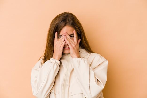 Giovane ragazza adolescente magra sbatte le palpebre alla telecamera attraverso le dita, imbarazzato che copre il viso