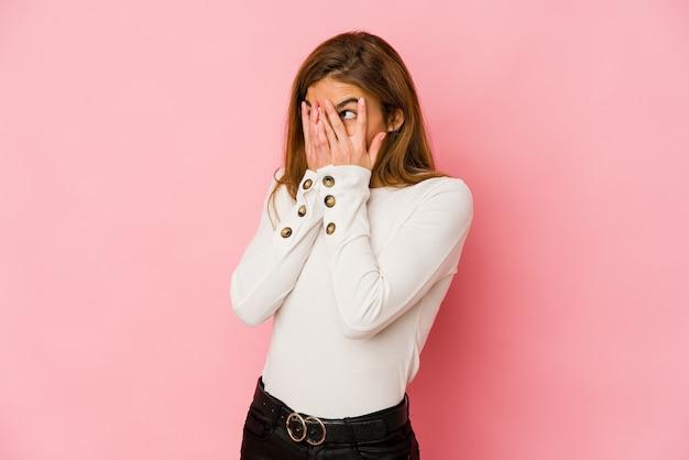 La giovane ragazza magra dell'adolescente sbatte le palpebre attraverso le dita spaventata e nervosa