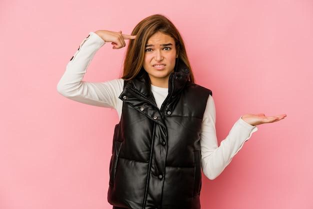 Ragazza giovane adolescente magra che tiene e che mostra un prodotto a portata di mano