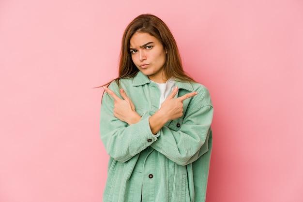 La giovane ragazza adolescente magra indica lateralmente, sta cercando di scegliere tra due opzioni