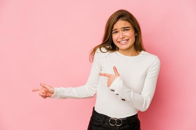 Giovane ragazza adolescente magra scioccata indicando con il dito indice a uno spazio di copia