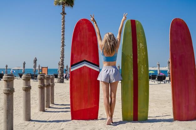 Una giovane donna magra sulla spiaggia in piedi accanto a grandi tavole da surf rosso e verde visto da dietro con le braccia in alto sopra la testa che mostra un segno di pace