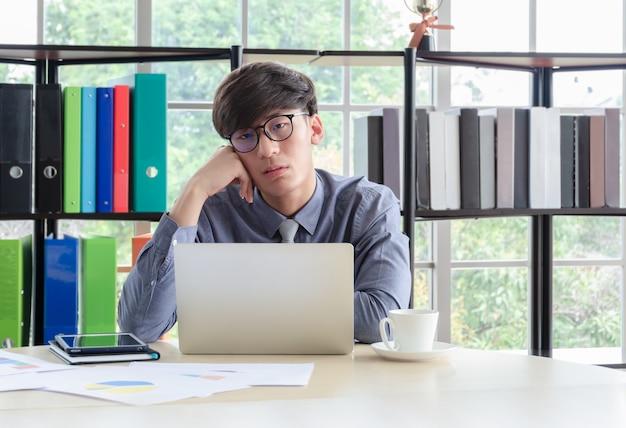 Giovane uomo d'affari assonnato con gli occhiali seduto e tenendo la testa a portata di mano davanti al computer portatile alla scrivania dell'ufficio
