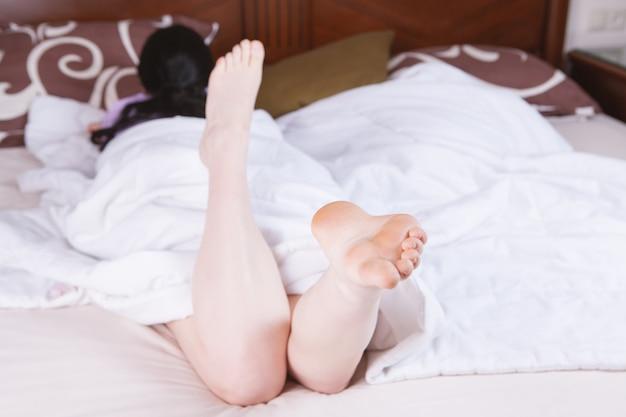 Una giovane ragazza snella e bella giace a letto