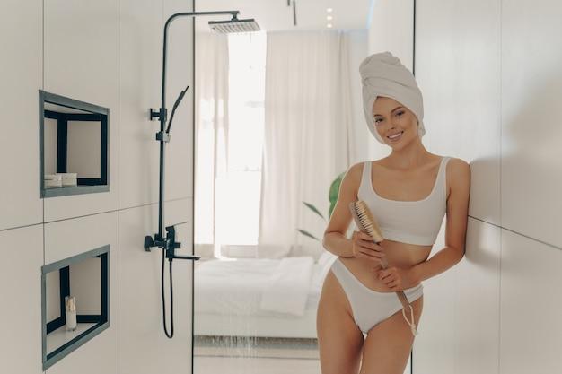 Giovane modello femminile snello in posa in un moderno bagno di colore chiaro indossa lingerie sportiva bianca e asciugamano avvolto sulla testa, tenendo una spazzola di legno per il massaggio a secco. trattamento di bellezza e concetto di cura del corpo