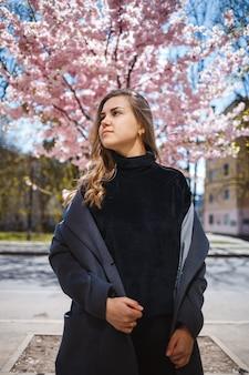 Una giovane modella snella con lunghi capelli ondulati e, vestita con un cappotto grigio, scarpe da ginnastica, si trova sulla strada vicino a un arbusto fiorito con bellissimi fiori rosa sullo sfondo e pose.
