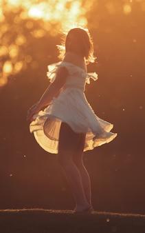 Giovane ragazza snella che balla al tramonto in abito bianco white