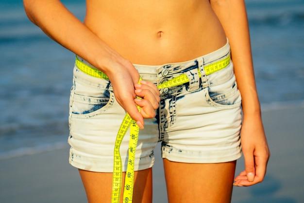 Una ragazza giovane e snella in pantaloncini di jeans tiene in mano un metro a nastro giallo sulle cosce sexy sulla spiaggia. concetto di disintossicazione e dieta