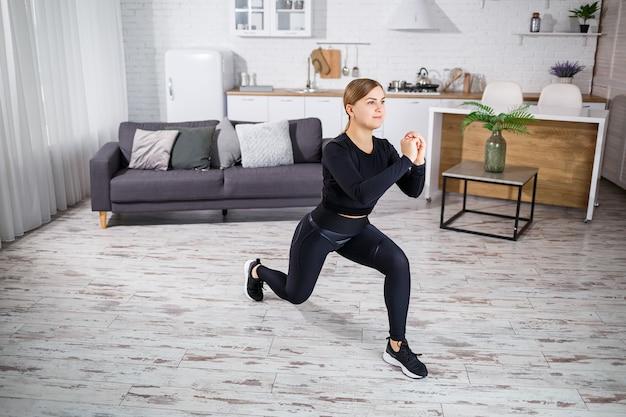Una giovane ragazza snella fa sport a casa, è vestita con abiti da fitness, un top nero e leggings. fitness a casa per un bel corpo