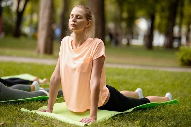 Giovane ragazza snella con gli occhi chiusi che fa esercizi di yoga sul tappetino da yoga sull'erba verde nel parco in una giornata calda. yoga all'aria aperta.