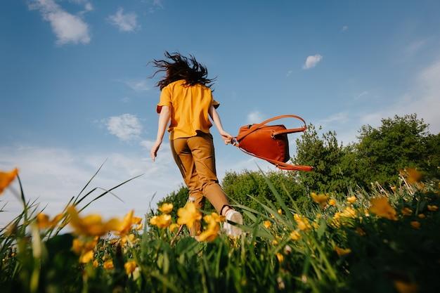 La giovane ragazza snella in un maglione giallo fa jogging allegramente su un prato verde nel parco con uno zaino in pelle vista dal basso gioia senza allergie da polline