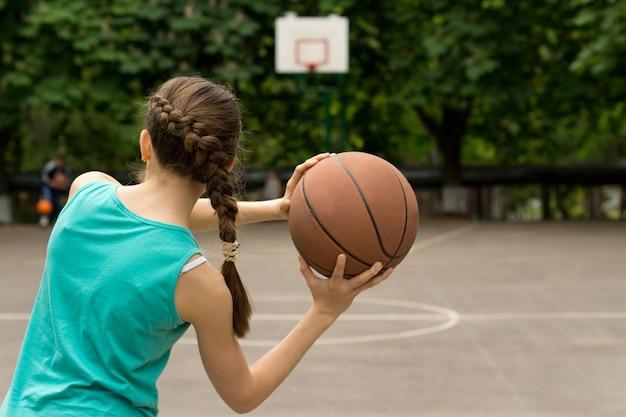 Giovane ragazza adolescente snella che gioca a basket lanciando la palla, vista da dietro