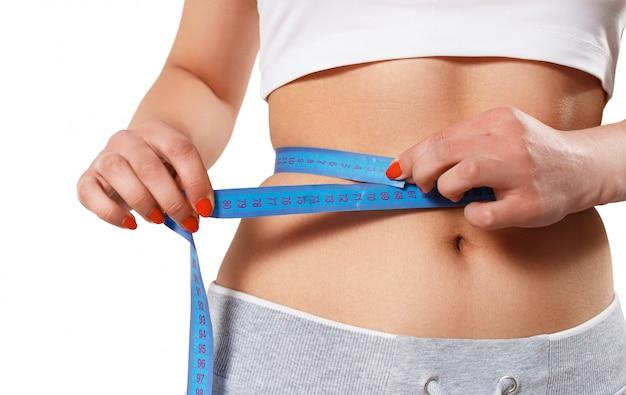 Una giovane donna snella misura la sua vita con un nastro di centimetri.